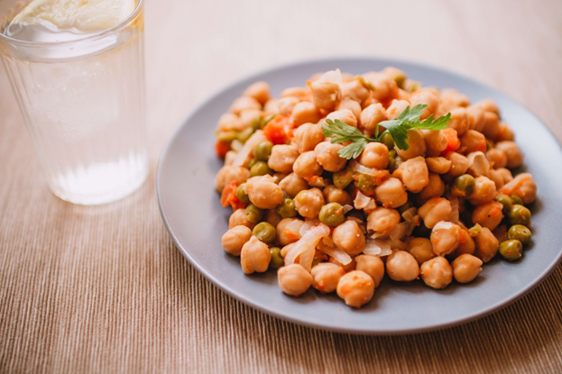 A plate of chickpeas and fried peas and a glass of water against a wooden background
