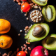 An assortment of oranges, avocados, chickpeas, apple, peanuts, and tomatoes against a dark background