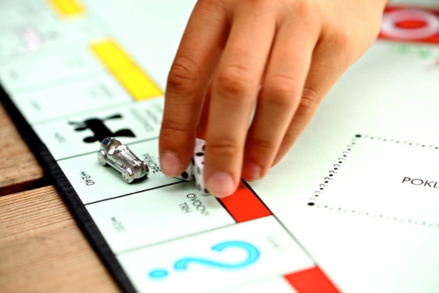 A person picking up dice lying on a board of monopoly with a miniature car on it