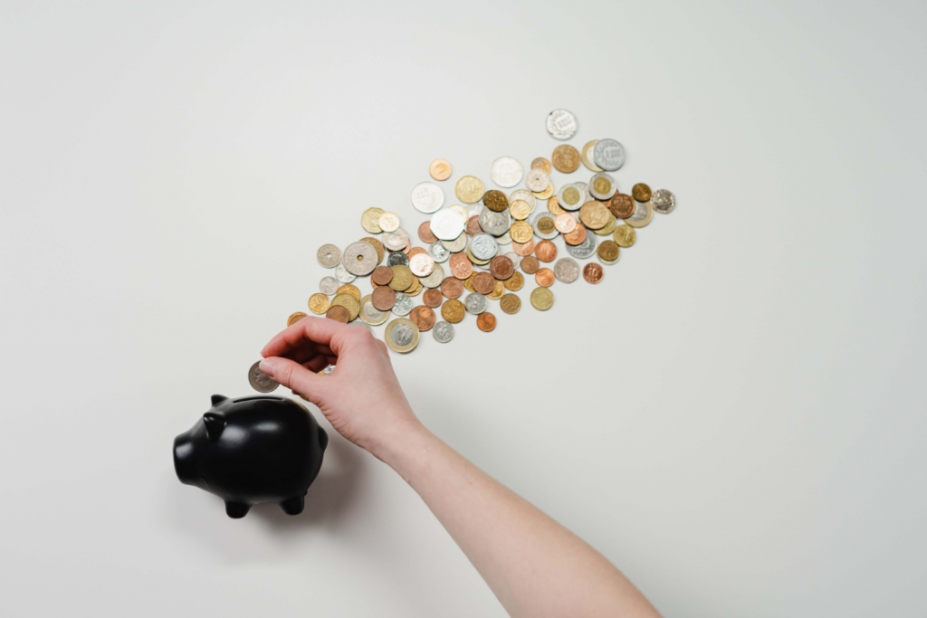 Putting money in a piggy bank with a pile of coins against a grey background
