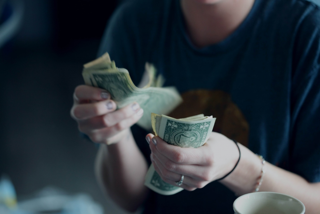 Someone in a T-shirt counting money against a blurred background